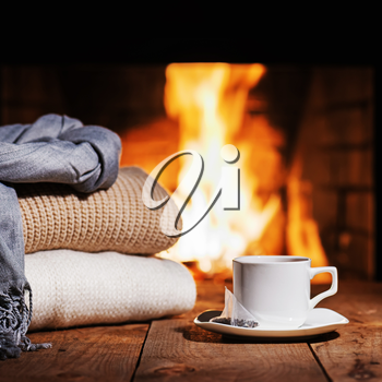 White cup of tea and warm woolen things near fireplace on wooden table. Winter and Christmas holiday concept.