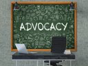 Green Chalkboard with the Text Advocacy Hangs on the Gray Concrete Wall in the Interior of a Modern Office. Illustration with Doodle Style Elements. 3D.