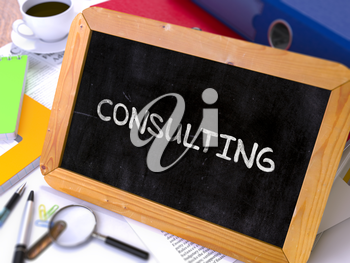 Consulting Concept Hand Drawn on Chalkboard on Working Table Background. Blurred Background. Toned Image.