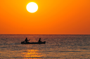 Royalty Free Photo of People in a Boat at Sunrise on Corona Beach, Panama.