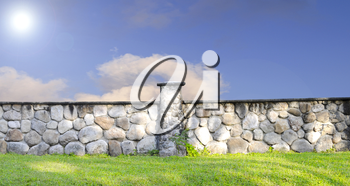 Stone  fence with green grass and blue sky