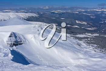 А view from the snow-capped Bliznitsa mountain (1881 meters above sea level) to the Dragobrat ski resort below. It is a great place for the freeride in Ukrainian Carpathian mountains.