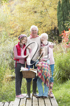 Grandparents With Grandchildren Carrying Picnic Basket By Autumn Woodland