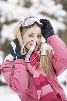 Teenage Girl Wearing Winter Clothes In Snowy Landscape