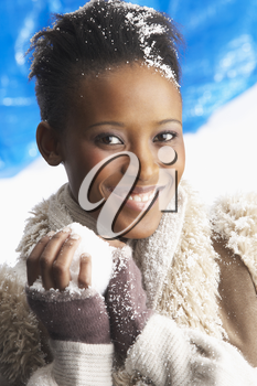 Young Woman Wearing Warm Winter Clothes Holding Snowball In Studio