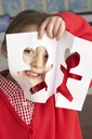 Female Primary School Pupil Cutting Out Paper Shapes In Craft Lesson
