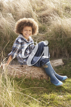 Young Boy Putting On Wellington Boots