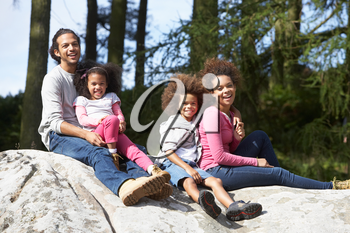 Family Group Sitting On Rock Together