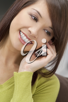 A beautiful young oriental woman with a wonderful smile chatting on her cell phone.