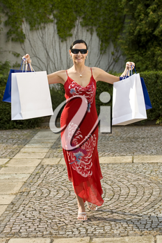 A classically beautiful woman clutching full shopping bags and looking happy