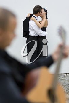 A young loving couple embrace while a street musician plays his guitar (out of focus) in the foreground