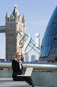 A beautiful young female executive using her laptop and mobile phone in front of Tower Bridge, Canary Wharf and the London city skyline