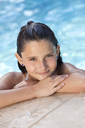 A cute happy young girl child relaxing on the side of a swimming pool