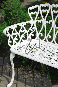 White wrought iron bench in a garden