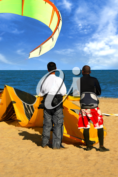 Two kite surfers standing on a beach watching on ocean