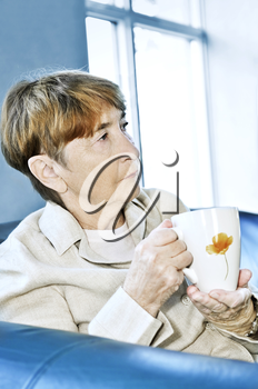 Sad elderly woman sitting with cup of tea