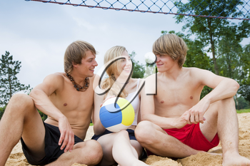 Group of three friends - one woman and two men - playing beach volleyball, the day is not overly sunny but they do not care and have fun nevertheless