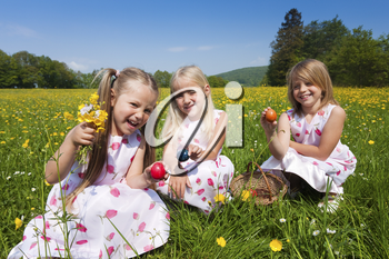 Children on an Easter Egg hunt on a meadow in spring