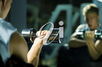 Young man with dumbbells, seeing himself in mirror (focus on dumbbells)