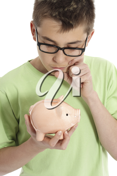 A boy holding a money box is thinking or pondering, eg finance, savings, spending.