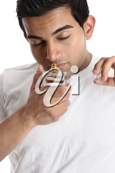 A man holds a bottle of perfume to his nose to smell the scent.