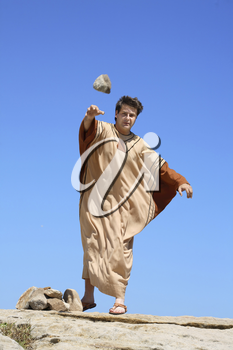 Depiction of ancient man throwing rock or stone.   concept sticks and stones, sin, condemnation, or historical reenactment.  Rock shows motion.
