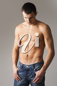 Image of shirtless man in jeans isolated over grey background