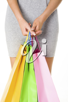 Close-up of female hands with colorful paperbags on background of her dressed figure