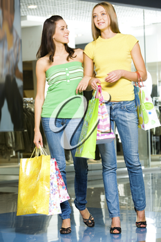 Image of two attractive women holding the bags and standing in the shopping mall