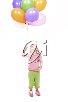 Image of small girl with helium balloons looking upwards at them
