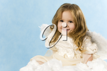 Happy little girl wearing angel dress sitting on white cloud and smiling