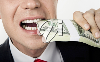 Close-up of male�s mouth biting bill of dollars