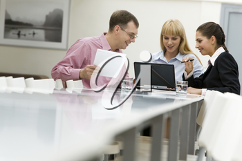 Image of business group communicating at the table and looking at laptop monitor in workshop