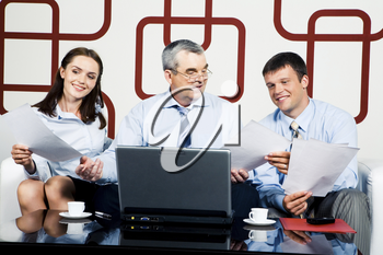 Adult businessman sitting at the table and giving documents to managers