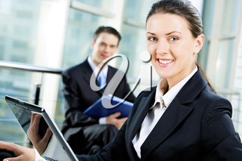 Confident business woman looking at camera during her computer work