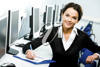 Portrait of smiling pretty student sitting at the table in the computer classroom on the background of computers and chairs