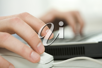 Close-up of human hand on white mouse during computer work