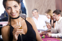 Portrait of pretty girl in black evening dress holding glass of champagne with her friends behind