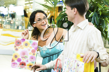 Image of beautiful girl looking happily at young man and laughing in the store