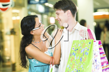 Portrait of a young couple carrying bags and looking at each other with smiles