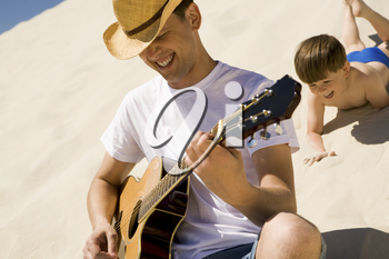Portrait of happy man in cowboy hat playing the guitar with his son at background
