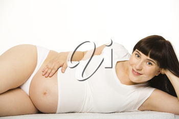 Happy pregnant woman lying and looking at camera on white background in studio