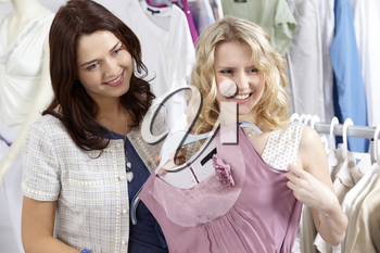 Image of pretty friends chosing new fashionable clothes in the department store
