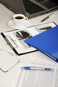 Business documents, laptop, eyeglasses, pens, folder and cup of coffee are lying on white table