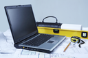 Photo of opened laptop with engineering objects and documents at workplace