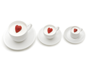 Row of three cups of different size with heartshaped berries inside them