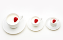 Three white cups of milk with heartshaped berries inside them