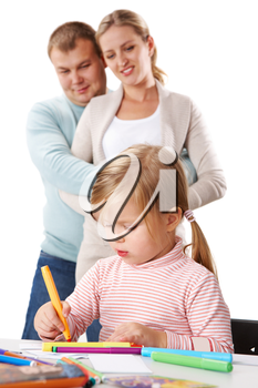 Photo of adorable girl drawing with highlighters with her parents behind