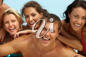 Portrait of joyful guy and happy girls on background looking at camera on summer vacation