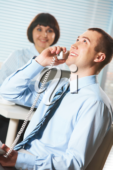 Portrait of happy businessman calling with secretary on background